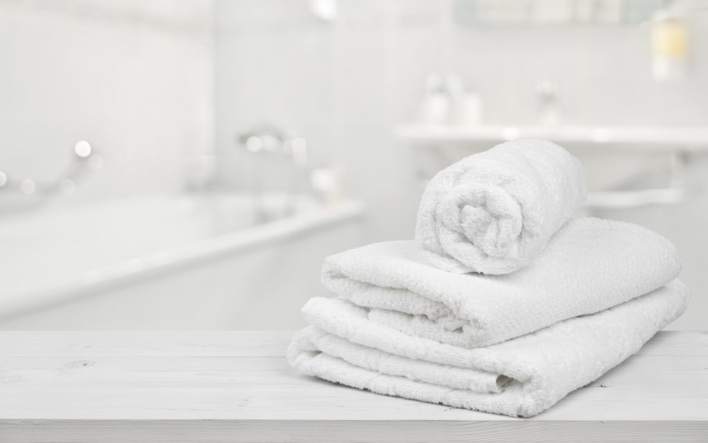 Stack of folded white spa towels over blurred bathroom background