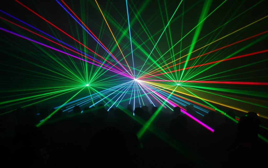 silhouetted people watching a fullcolor laser beam-show
