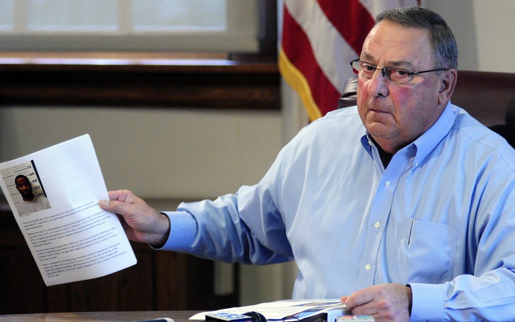 Maine Gov. Paul LePage holds up news release with a booking mug shot from a three-ring binder of news releases and articles about drug arrests during a meeting with reporters on Friday, Aug. 26, 2016, in the State House Cabinet room in Augusta, Maine. (Joe Phelan /The Kennebec Journal via AP)