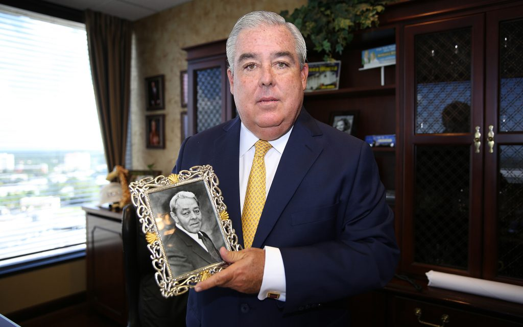 Florida attorney John Morgan holds a photo is his late father Ramon, who passed away from cancer. This image of him was taken in his office at the Morgan and Morgan law firm in Orlando, Florida on Tuesday, September 2, 2014. (AP Photo/Alex Menendez)