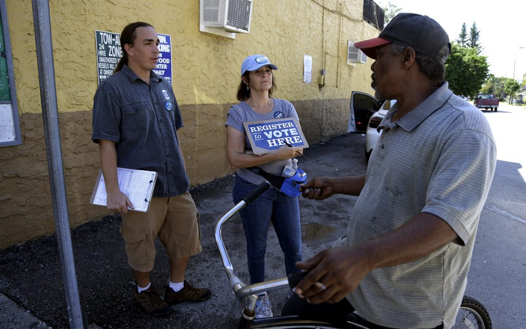Volunteers walked neighborhood streets to register voters as Tuesday is the last day to register to vote in the general election Nov. 6. Monday, Oct. 8, 2012 in Miami. (AP Photo/Lynne Sladky)