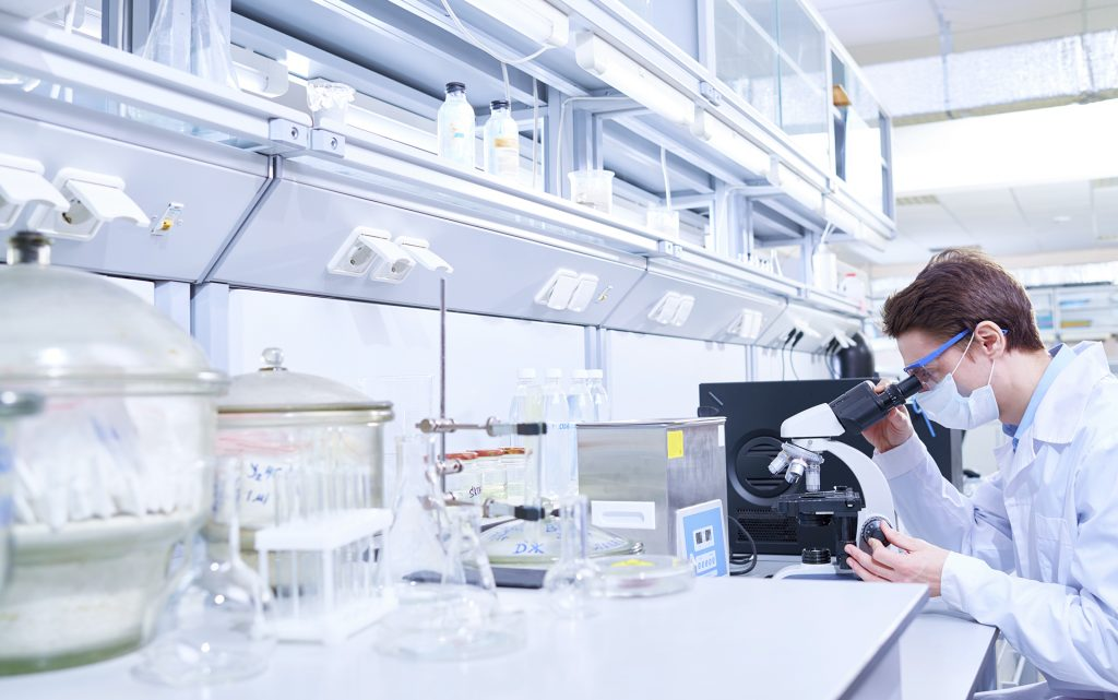 Young scientist examining sample with microscope in modern laboratory.