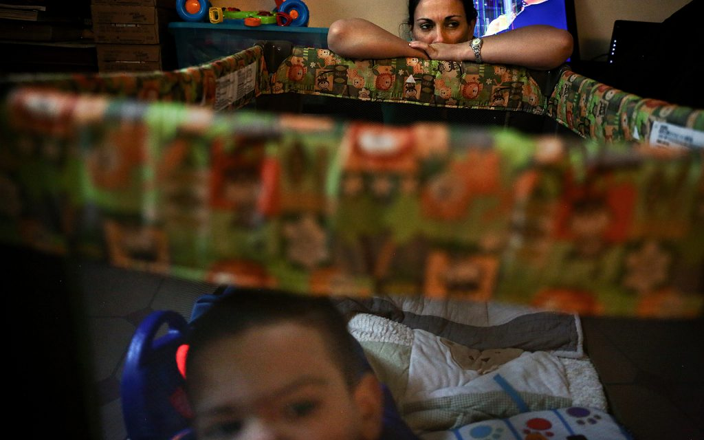While Bruno Stillo moves about in his playpen, his nurse Idania Gonzalez takes a brief rest while watching over him in their Miami, FL home on Friday, October 28, 2016. When his mother isn't watching over him, Gonzalez is always watching to make sure he's safe. (Scott McIntyre for Leafly)