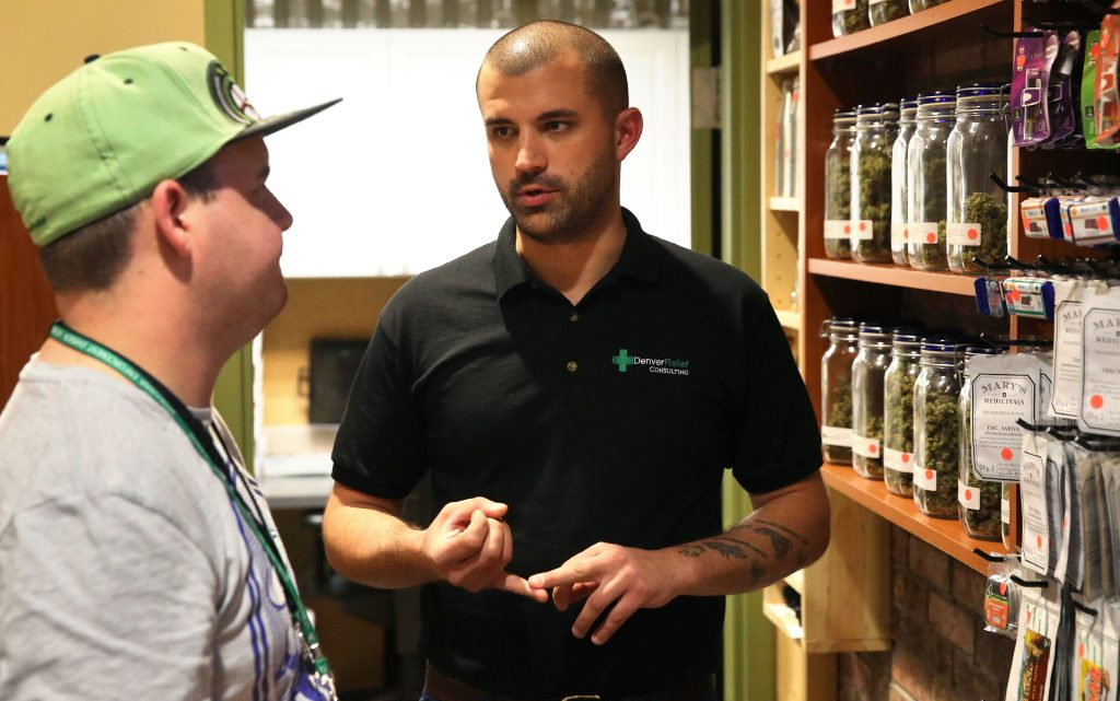 Denver Relief co-owner Kayvan Khalatbari, right, talks with his employee Jeff Botkin at his shop in Denver. (AP Photo/Brennan Linsley, File)