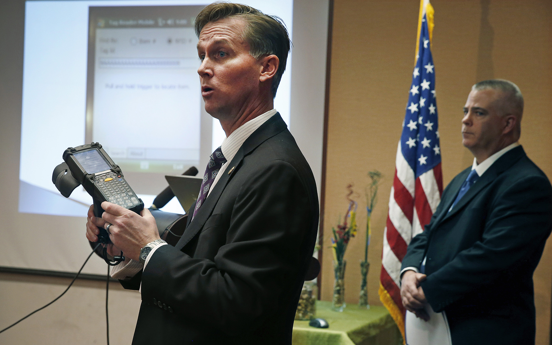 Lewis Koski, left, chief investigator of the Colorado Marijuana Enforcement Division, demonstrates a handheld radio-frequency reader, which is part of its new marijuana inventory tracking system, known as MITS, during a news conference, in Denver, Wednesday, Dec. 11, 2013. Ron Kammerzell, the senior director of enforcement for the Colorado Dept. of Revenue, is pictured at right. Roughly 150 Colorado medical marijuana dispensaries are hoping to begin selling to recreational users when it becomes legal to sell on Jan. 1, 2014. (AP Photo/Brennan Linsley)
