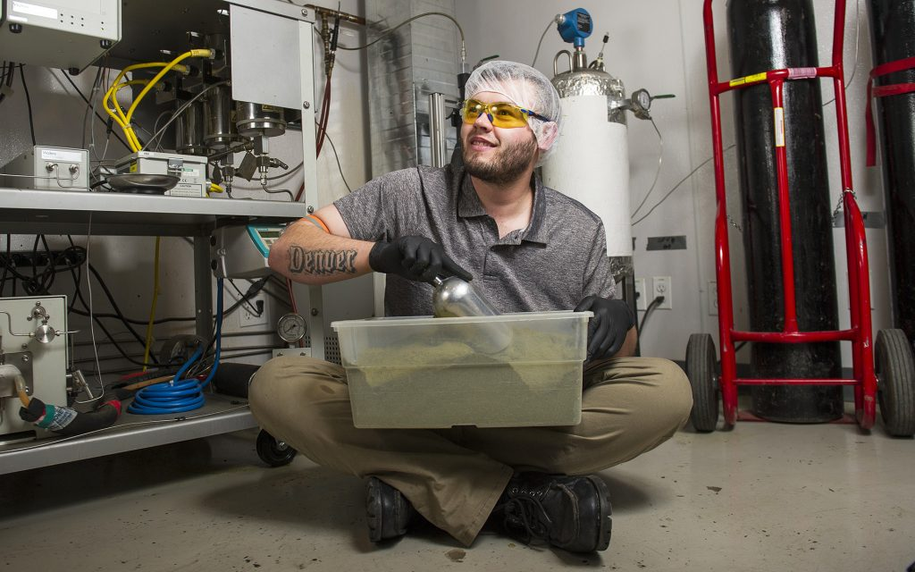 "Extraction tech Chris Moder poses for a portrait Friday, Dec. 30 2016 at Dixie Elixirs in Denver, CO. He has worked for the company for six years and uses a ""super critical CO2"" method to separate cannabinoids. Moder explains the method is a clean, well-tested extraction process to obtain pure THC. ""It's what gives it power,"" he said. ""I used air to make that, high five!"""