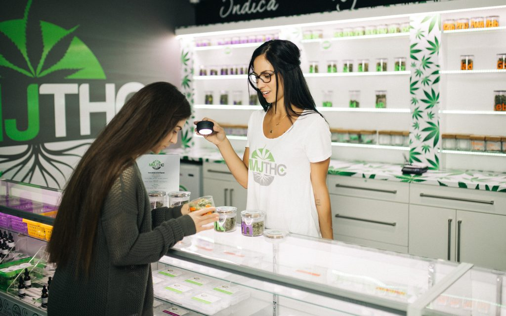 Budtender showing customer cannabis at MMJ Total Health Care in British Columbia