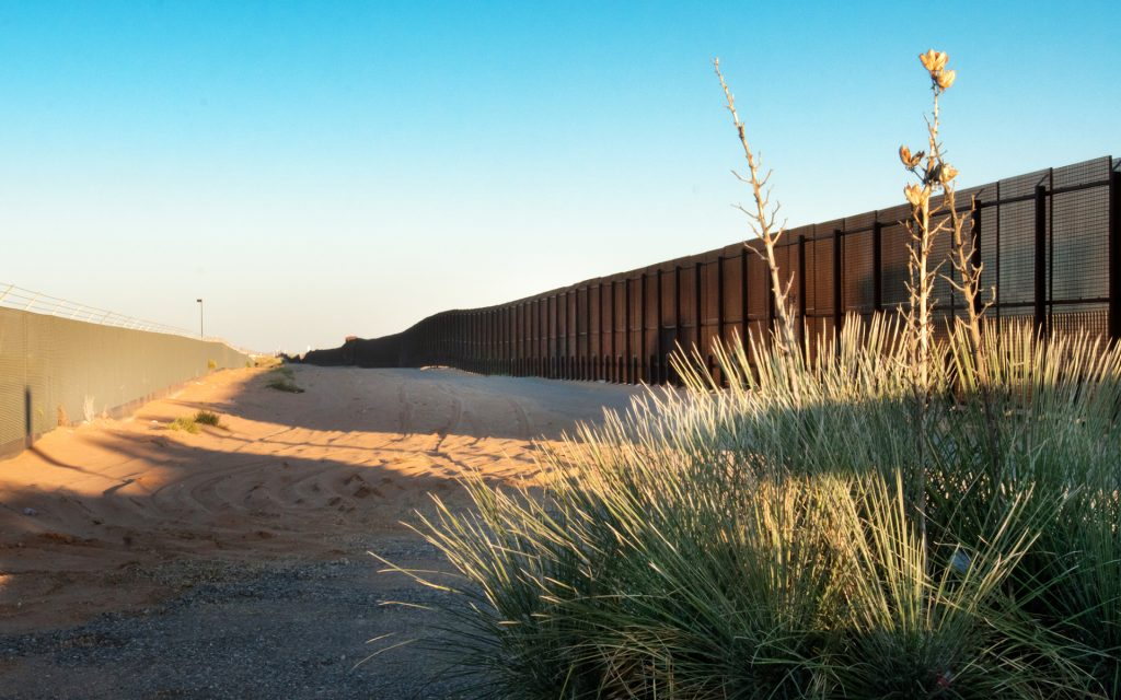 Wide angle shot of the border between Mexico and USA with bush in the foreground and a clear blue sky at dusk
