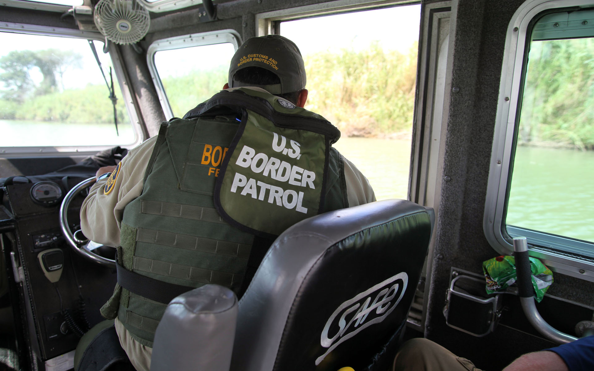 La Paloma, Texas, USA - September 22, 2015: A Border Patrol agent pilots a river patrol boat and monitors the Rio Grande River for illegal aliens crossing into the U.S. Such encounters are a daily experience in the Rio Grande Valley sector of Border Patrol operations.