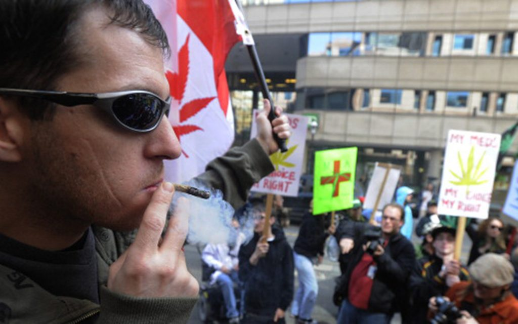 April 11, 2010. Christopher Goodwin smokes cannabis outside police headquarters on College St. to protest a recent raid on their medical marijuana club. (Colin McConnell/Toronto Star/Getty Images)