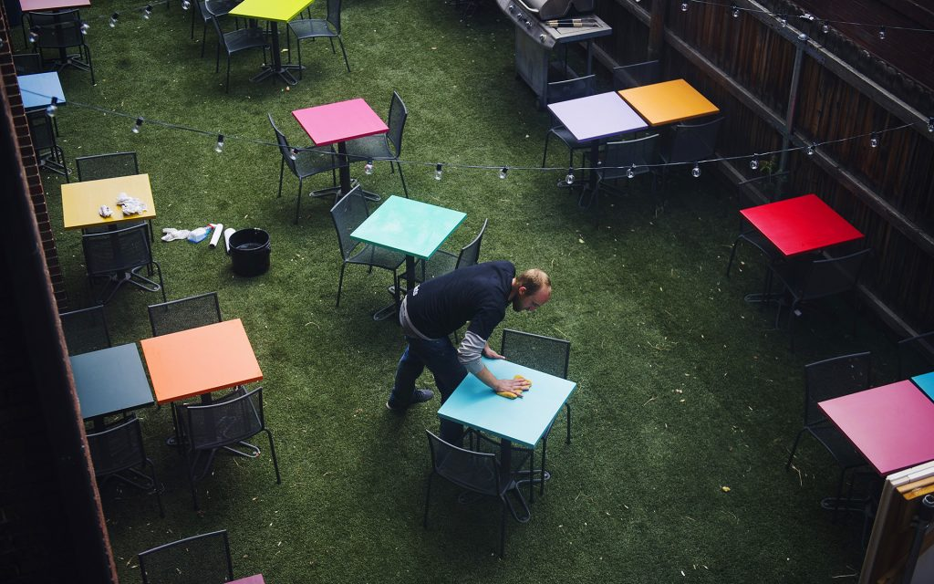 Co-founder Zach Gardner wipes down tables outside on opening day of the International Church of Cannabis (Daniel Brenner for Leafly)