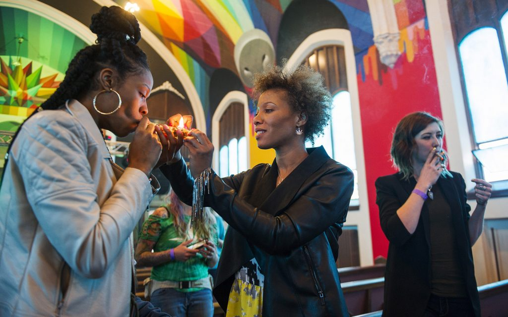 Chicago resident Andrea Camp, from left, gets a light from Lakewood resident Kimm Miller, as Mia Jane smokes at a private viewing on opening day of the International Church of Cannabis. (Daniel Brenner for Leafly)