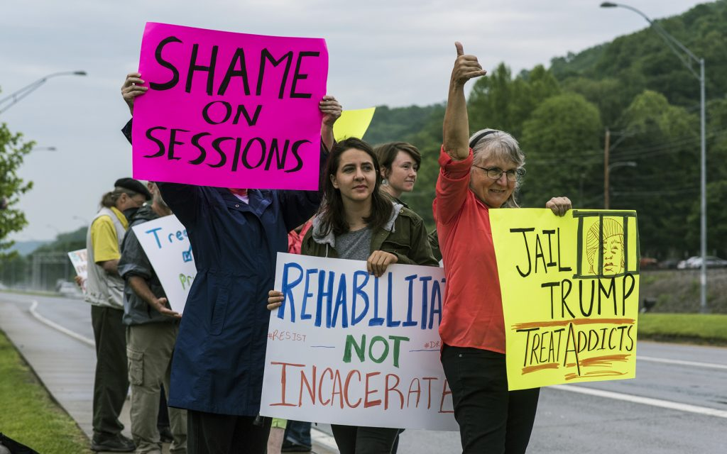 Protestors hold up signs as they await the arrival of Attorney General Jeff Sessions, who gave opening remarks during a Drug Enforcement Administration (DEA) 360 Heroin and Opioid Response Summit at the University of Charleston, Thursday, May 11, 2017, in Charleston, W.Va. The event, which was sponsored by the DEA, Community Anti-Drug Coalitions of America and the University of Charleston School of Pharmacy, was held to provide solutions and strategies for combating the heroin and prescription drug abuse epidemic. (AP Photo/Sam Owens)