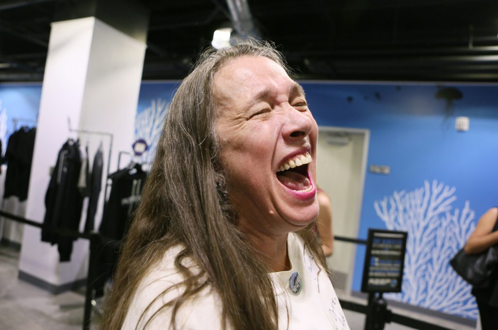 Customer Marilyn Uldricks laughs while speaking to the news media after making a purchase shortly after legal sales began early Saturday morning. (Ronda Churchill for Leafly)