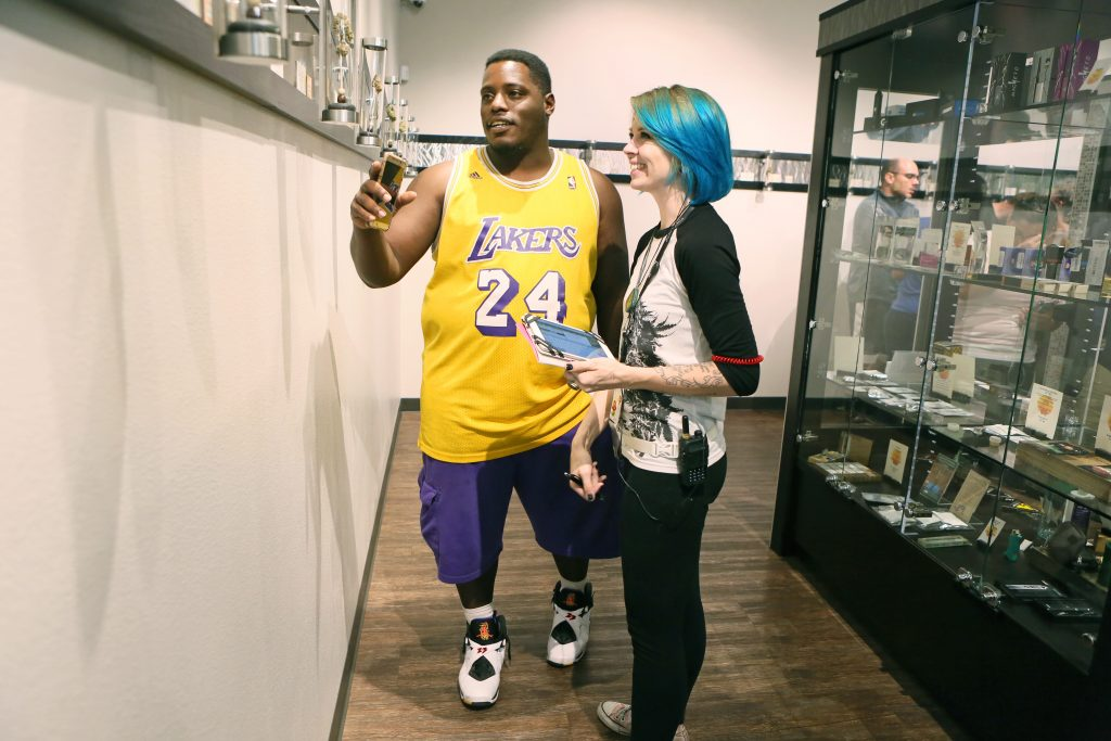 Customer Anthony Ramsey, left, of Las Vegas, receives guidance from staff member Aly Bessey at Oasis Medical Cannabis early Saturday morning. (Ronda Churchill for Leafly)