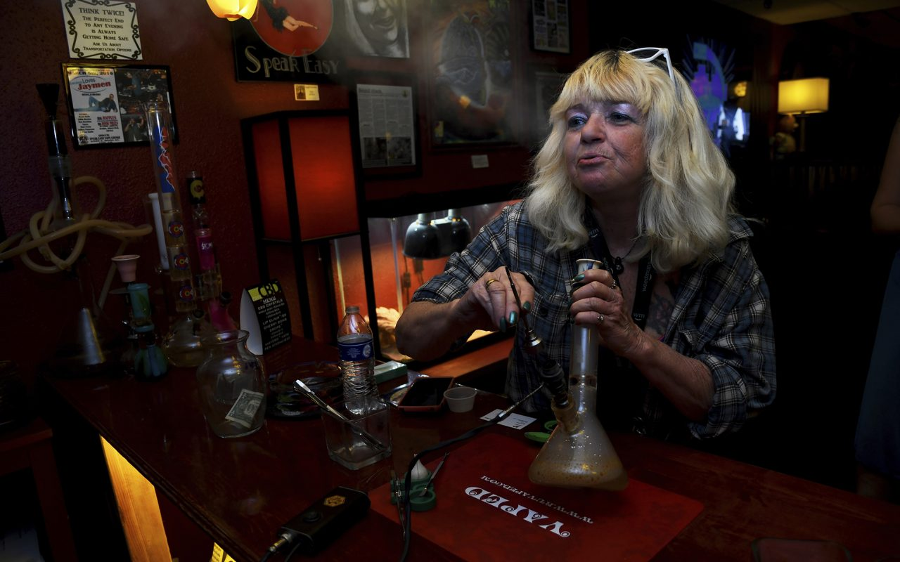 "In this April, 12, 2017 file photo, Linda Wood smokes a concentrated form of marijuana called a ""dab"" at the Speakeasy Vape Lounge, one of the United States"
