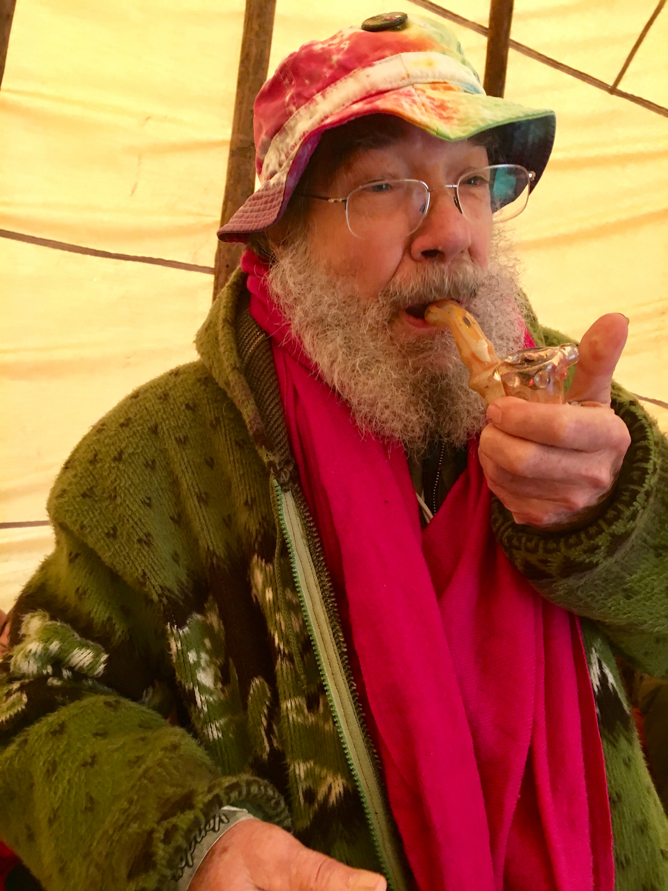 Borosilicate glass pipe pioneer Bob Snodgrass hits a piece made by his son in the Dragonfly Earth Medicine Tent Sunday. (David Downs/Leafly)