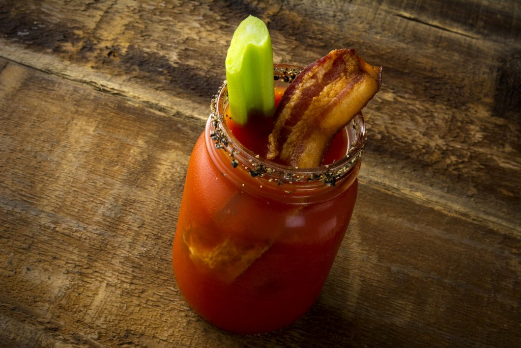 caesar cocktail Two mason jar Bloody Mary or Caesar with bacon on wood background