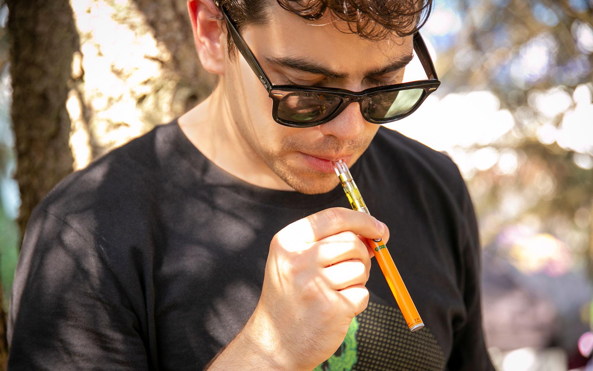 man in sunglasses vaping cannabis oil