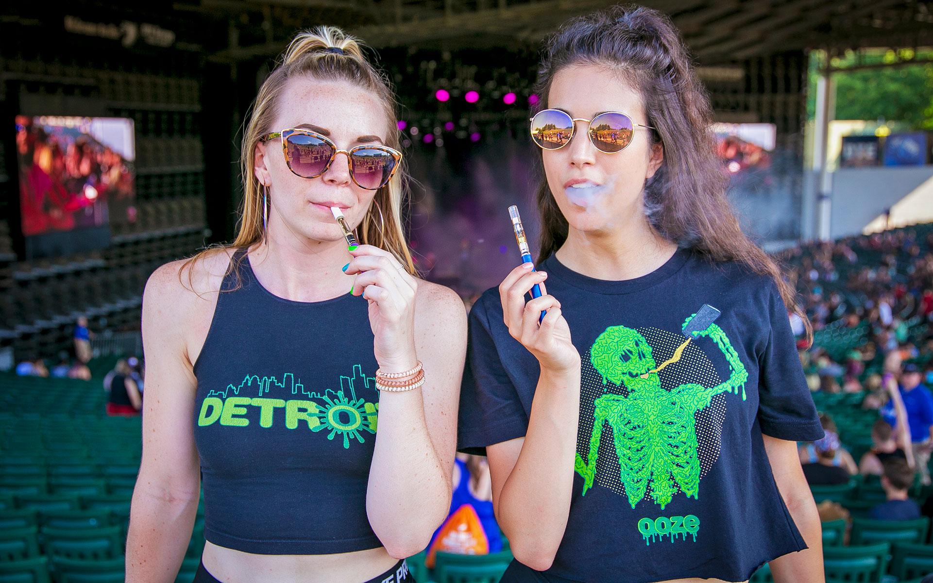 two women using ooze vape pens at a festival