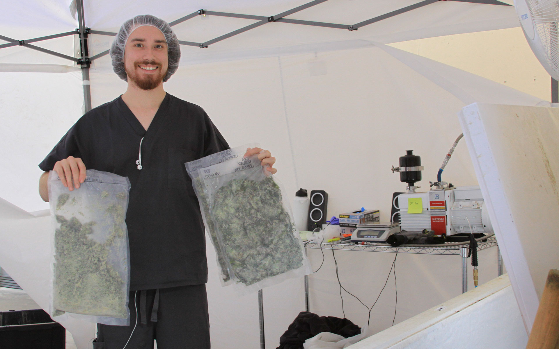 A Utopia Cannabis technician holds up bags of fresh-frozen cannabis. (Courtesy of Utopia Cannabis)