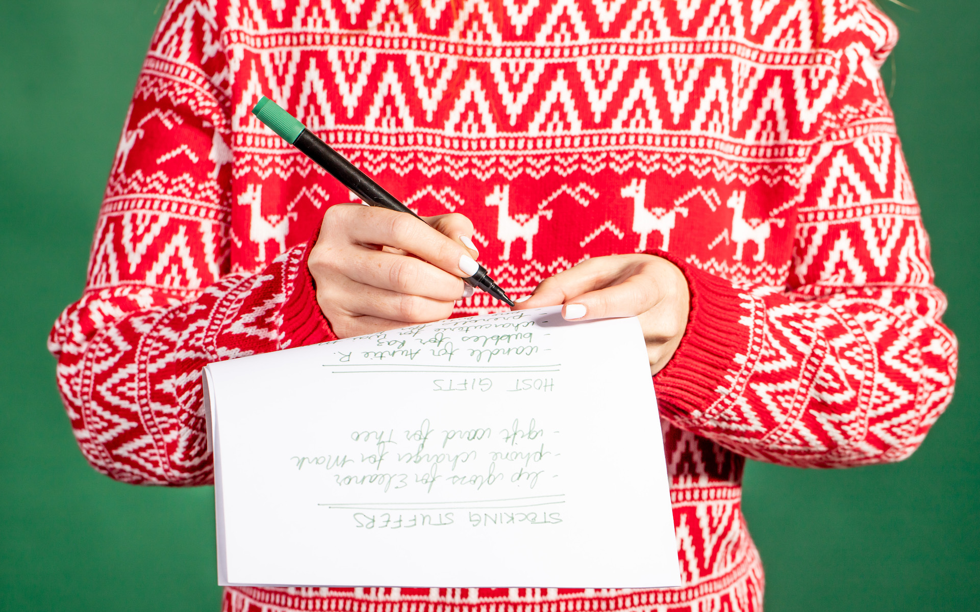 Cannabis holiday etiquette; person in Christmas sweater writing gift list