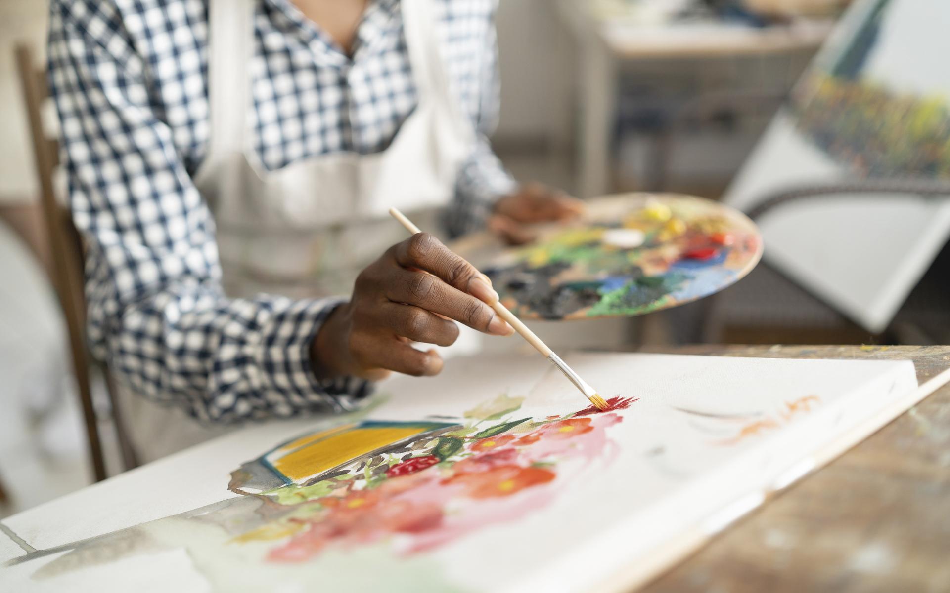 Female artist working in studio, drawing flowers.